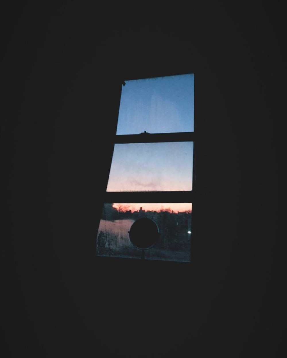 A picture of a light coming through a window. Everything is Black except for the Window. outside the window there's a bit of silhouette of cityscape and a gradient of setting sun, orange fading into blue. Sitting at the bottom of the window sill is a small vanity mirror.