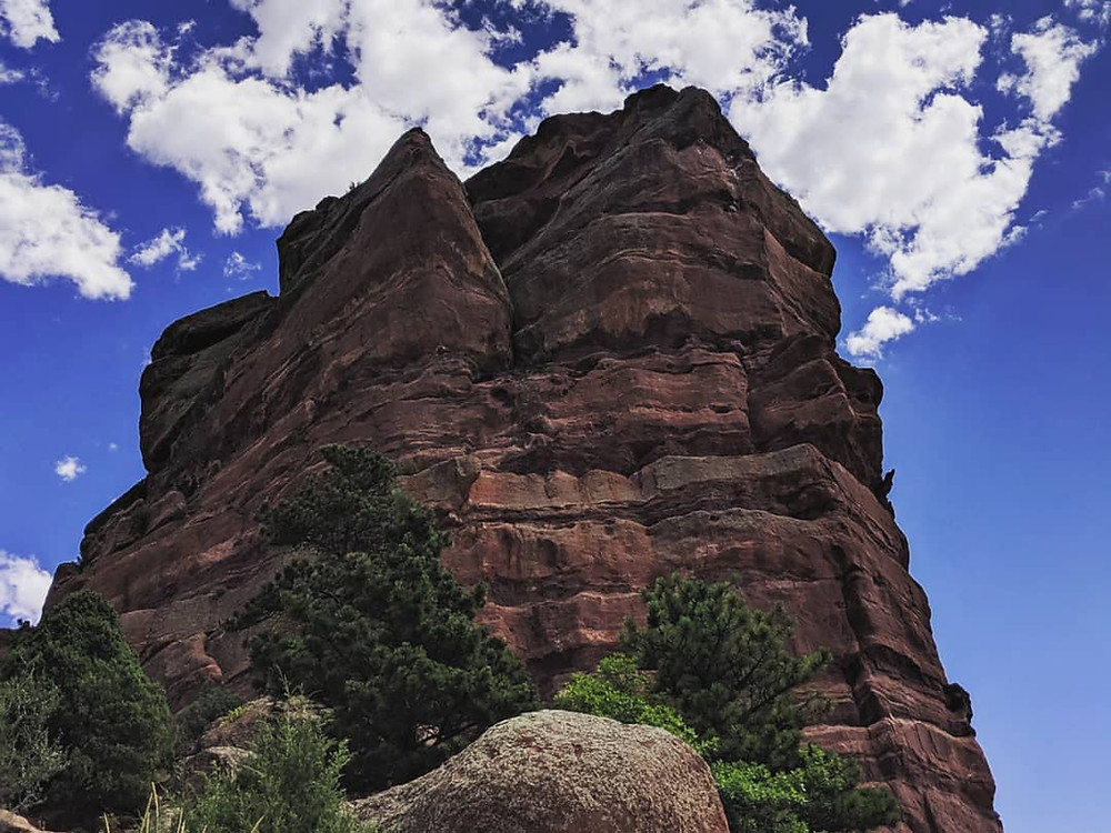 A photo of a large reddish rock formation, maybe about 200 ft tall, against a bright blue sky with contrasting fluffy clouds behind. In front of the rock are a few green trees and bushes and a smaller lighter colored rock. Photo taken on ancestral homelands of the Cheyenne and Arapahoe Nations (near Denver, CO)