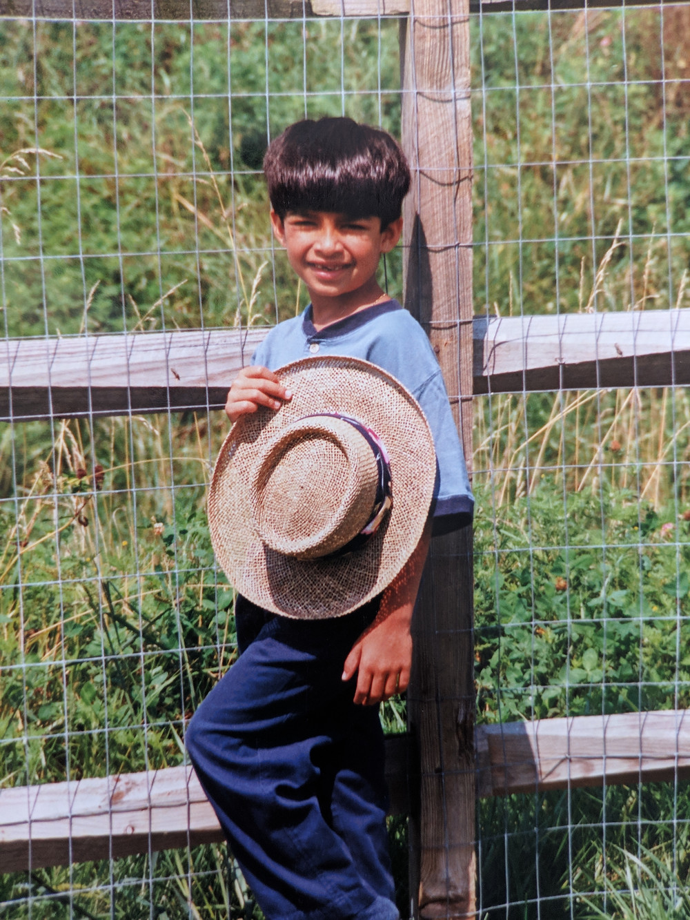 A six-year-old Uliya with a bowl cut stand against a brown wood fence with wire mesh. Behind then is a field of tall grass. They are holding sun hat and wearing blue pants and a light blue shoot.