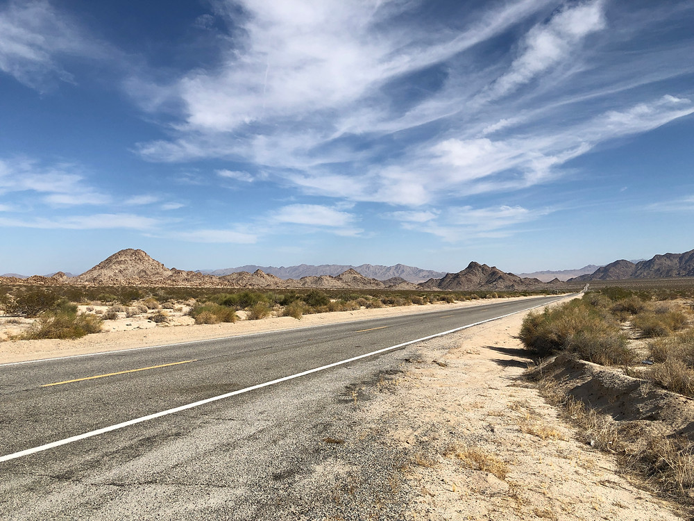 Lightly-clouded blue sky and California desert, featuring a highway