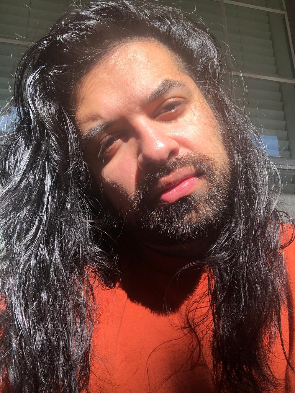 Uliya with long black hair and an burnt orange shirt
