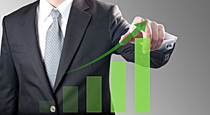 Business man pointing at green bar chart