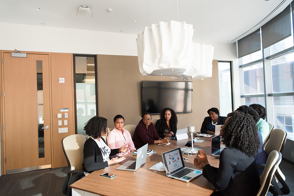 An office space with light wood, natural light, big windows, and white lamps hanging from the ceiling. Around a large boardroom table sit Black women with open laptops, talking.