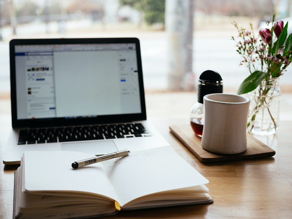 An open Macbook  and notebook with a pen, alongside a cup of coffee and flowers on a well-lit wooden desk