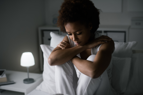 A person sits up in their bed in the middle of the night, with their bedside lamp on, arms crossed, and looking down at the bed with a concerned look on their face.