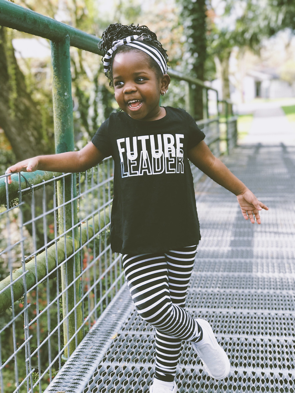 """A toddler stands on a bridge in a park with her legs crossed and a smile on her face. On her t-shirt, it says: """"Future Leader"""""""