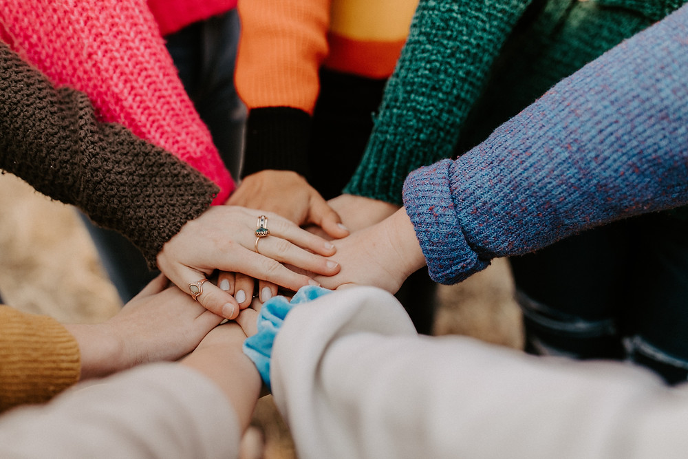 A pile of hands are all in the center, each with different colored sweater sleeves in brown, red, green, blue, orange, cream, and yellow.