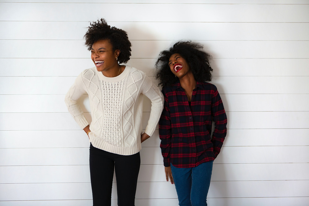 Two people in sweaters stand against a plain white wall. They're both looking to the left and laughing.