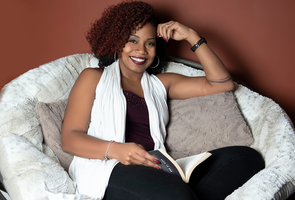 ZeNai Brooks sits down on a chair with a book open in her lap.