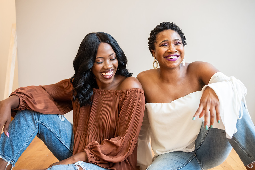 Two women sit on the ground laughing.