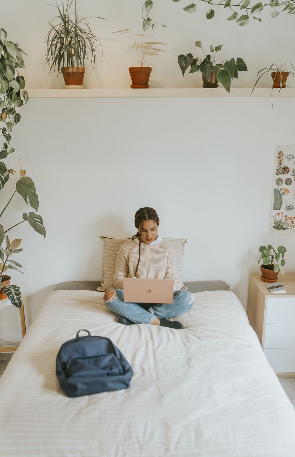 woman sitting on bed with laptop surrounded by plants