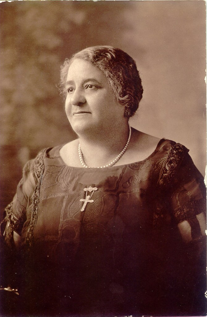 A black and white photo of Maggie Lena Walker looking to the left side of the frame with a cross and pearls around her neck.