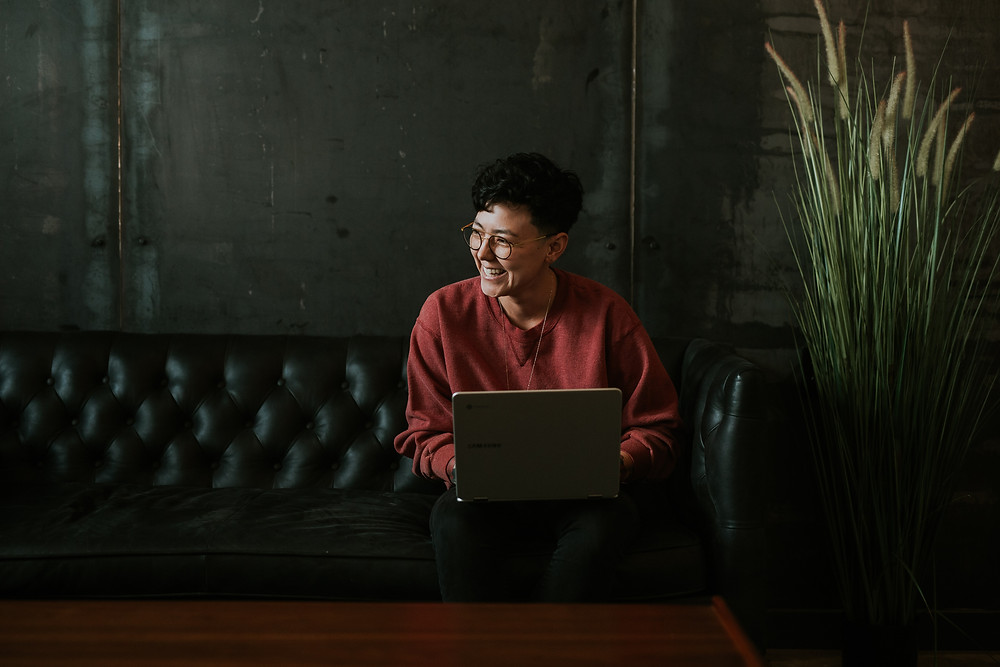 A person in a red sweater, short black hair, and glasses sits on a black leather couch with a laptop on their lap. They're looking to the left and laughing. behind them is a dark gray wall, to the right of them is a plant, and in front of them is a long, wooden coffee table.