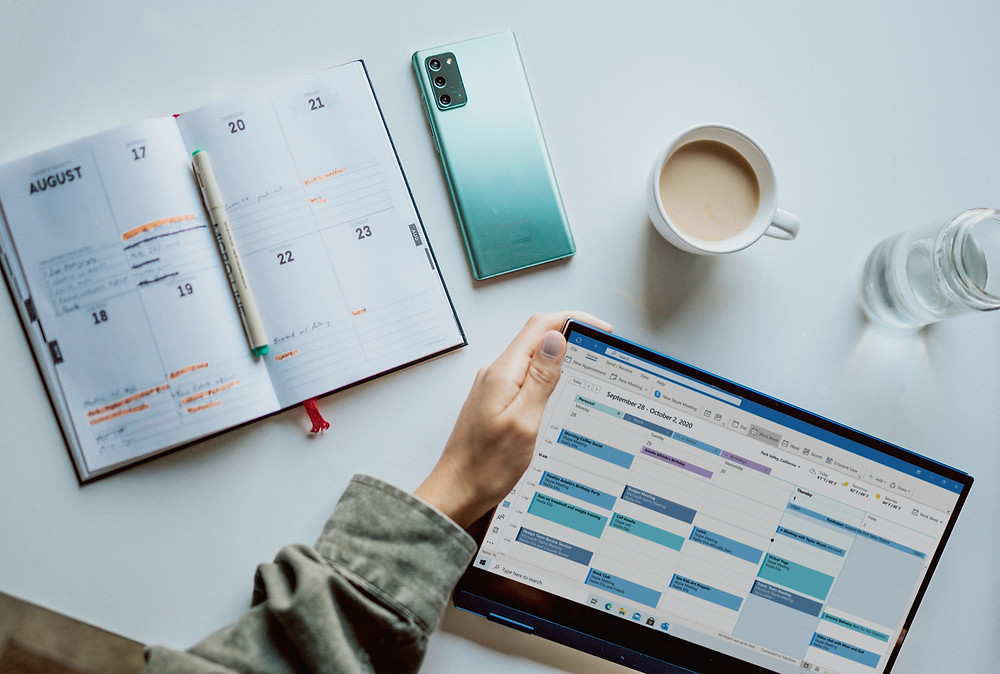 A white desk with a planner lays open, with tasks highlighted in. There's a pen resting in the center of the planner. To the right of the planner is a blue phone. There is a hand holding a tablet with a calendar of events open. There's a cup of coffee in front of the tablet as well as a glass of water.