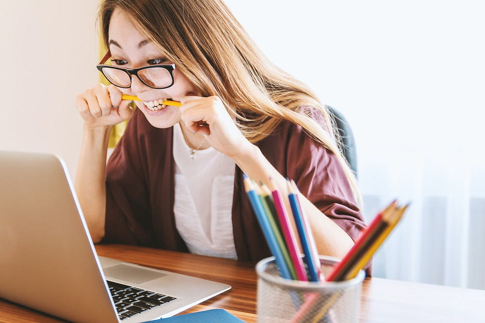 A person wearing glasses and a burgundy cardigan stares at their open laptop while biting their pencil in frustration. There is a cup of more pencils next to them.