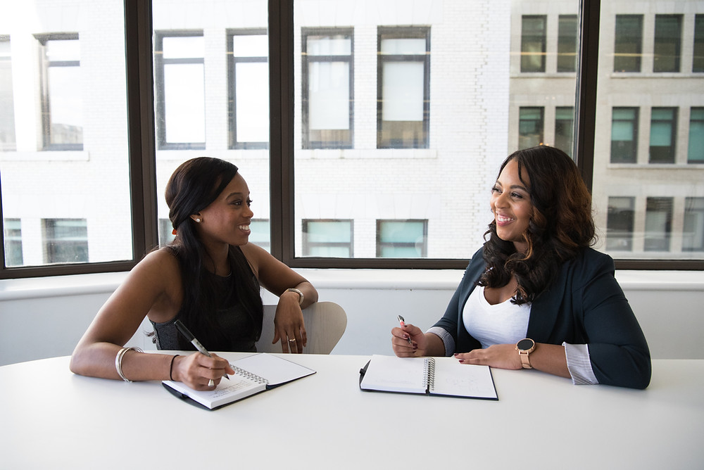 Two Black women sit at a table in an office space talking and laughing. They both have pens in their hands and open notebooks. A large window with a view of other buildings is behind them.