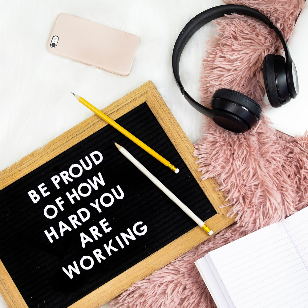 """A letterboard says: """"Be proud of how hard you are working"""" in white text, black ground, with a wooden frame and two pencils askew on top of the board. Underneath is a white desk and light pink fluffy blanket. There is a light pink cell phone laying face down on the white desk, black over the ear headphones lying on the white desk and pink blankets, and an open notebook on the blanket."""