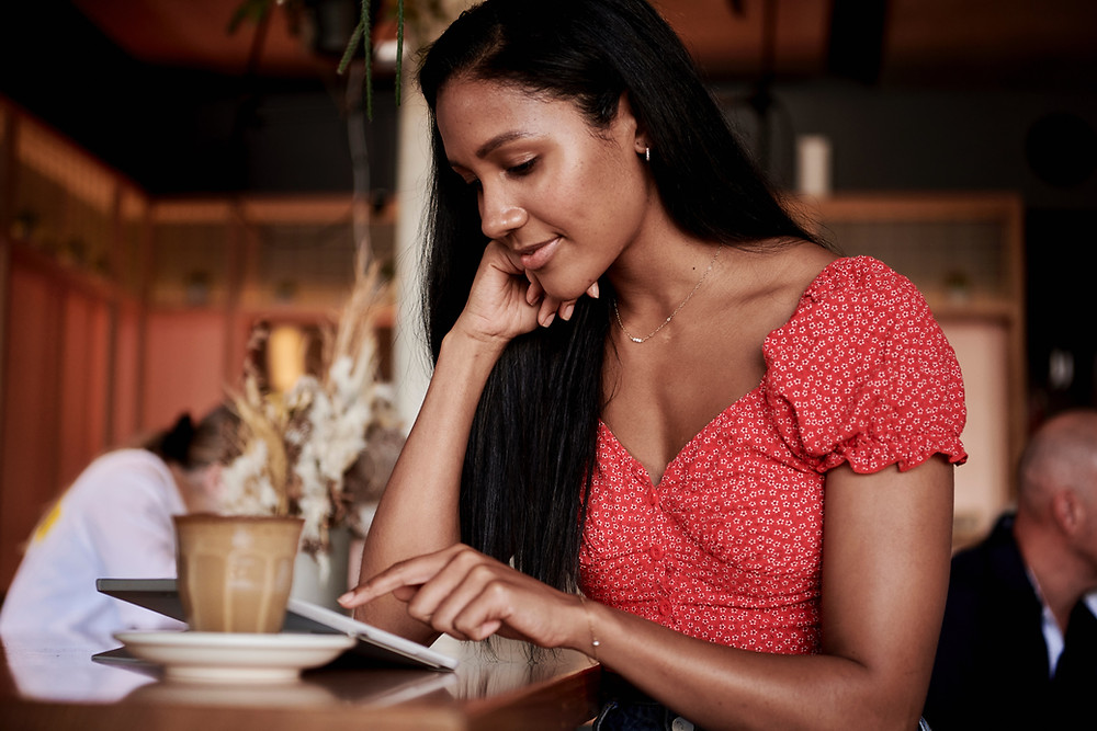 A Black person in a red dress and long Black hair sits at a coffee shop with a mug on one side and an open tablet.