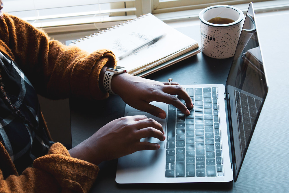 A close up of a Black woman's hands as she types on her laptop. A cup of coffee, open notebook, and a pen are next to her on the desk.