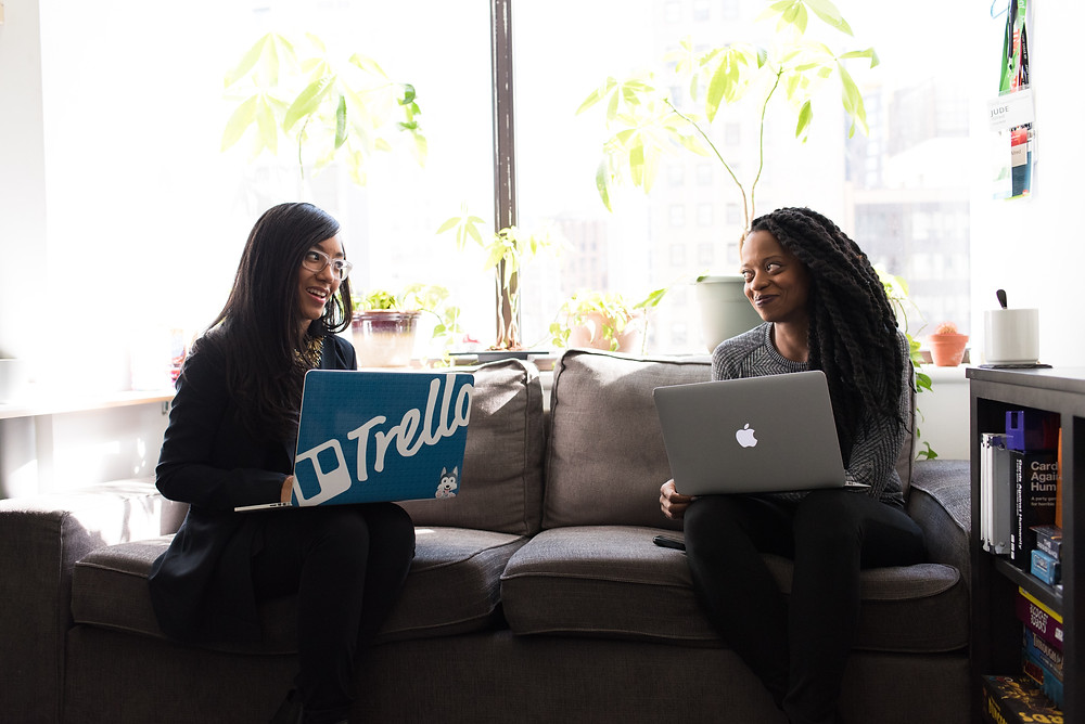 Two Black women with their laptops open sit on a grey couch in mid conversation. A big window is behind them with plants.