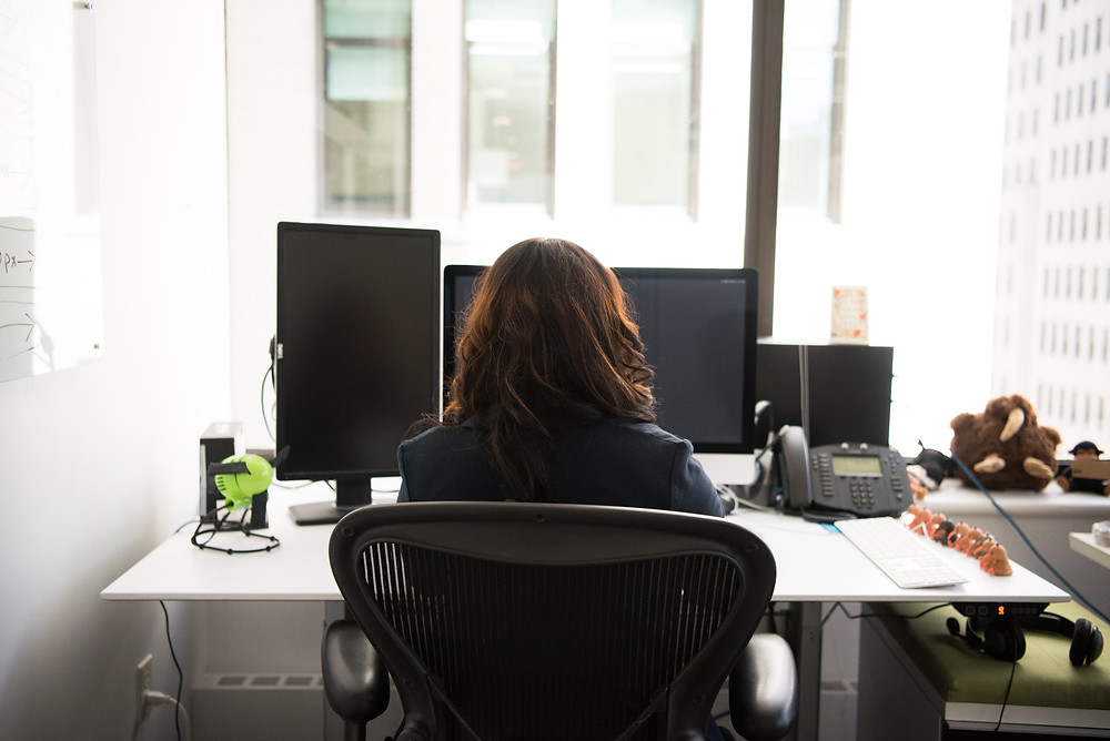 A view from behind of a woman in a suit seated at a desk with a computer.