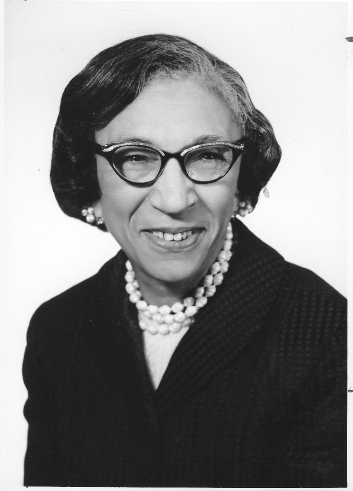 A black and white photo of Viola Turner in pearls and glasses.