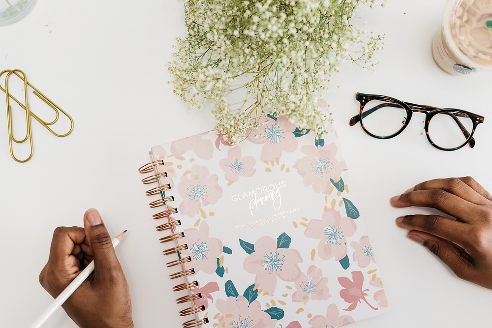 An aerial view of a desk with a journal, glasses, gold paperclips, a Starbucks coffee, a plant, and two hands around the journal holding a pencil.