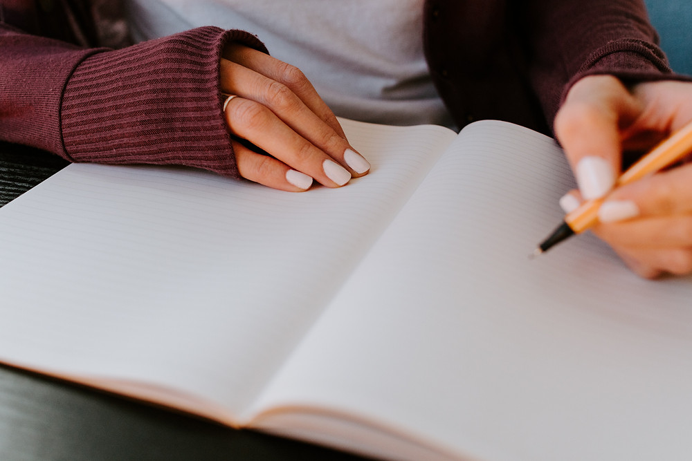 A close up of person writing in a lined journal. In one hand, there is an orange pen, while the other hand holds the notebook down. The person is wearing white nail polish, a gold ring on their ring finger, and a maroon cardigan with a white shirt underneath.