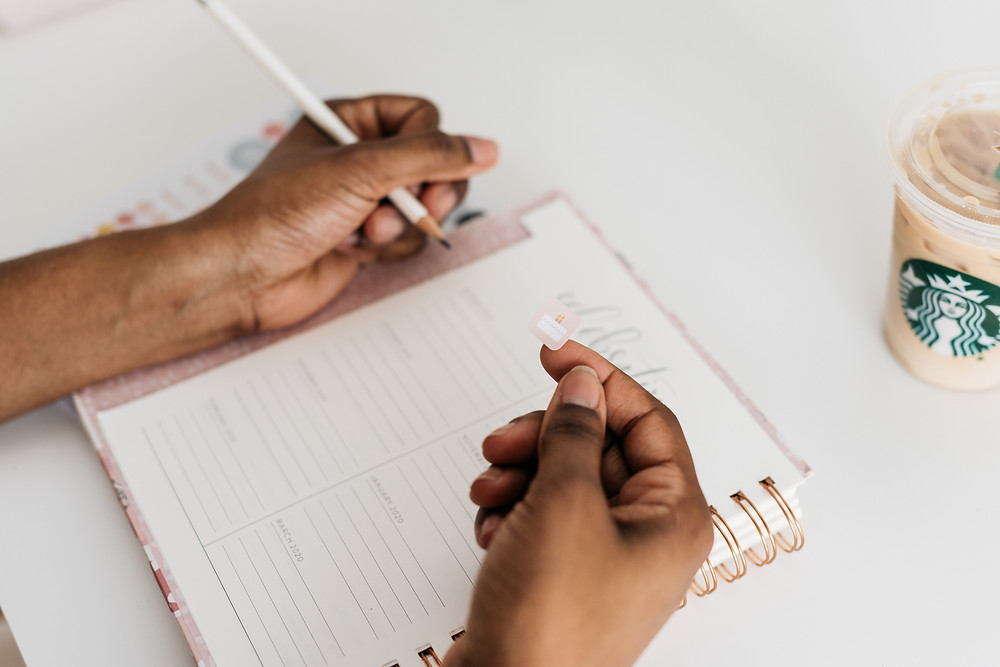 A close up of hands writing down in a journal. There is a cup of Starbucks coffee next to the journal.
