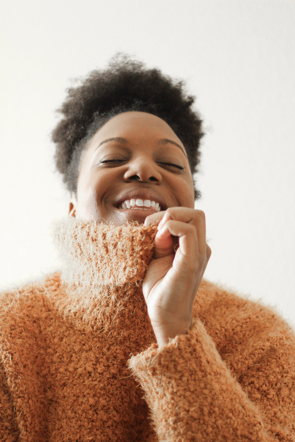 A person in a fluffy orange turtleneck smiles with their eyes closed as they pull the neck of the sweater up over their mouth.