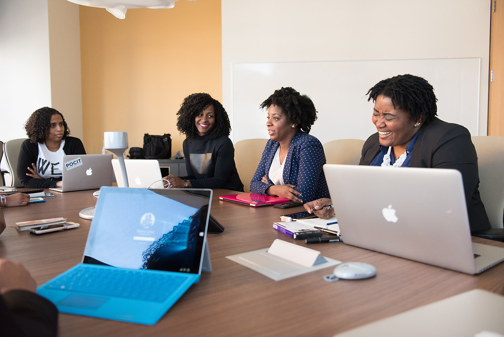 Five Black women sit around a large office table with open laptops, talking and laughing.