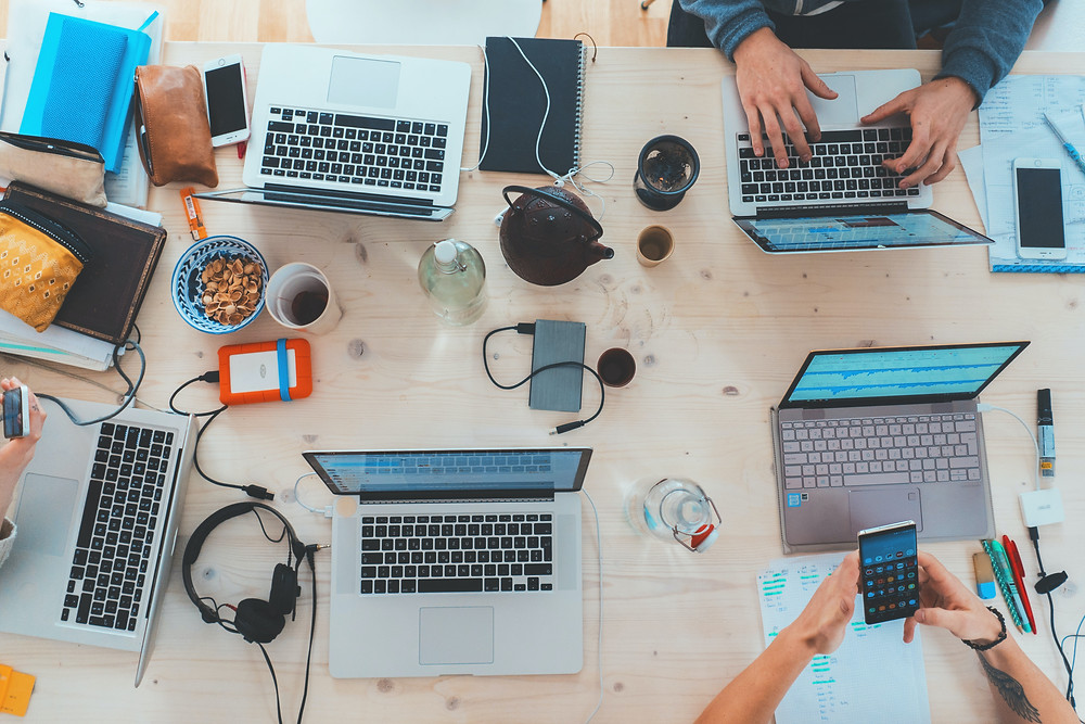 A pine table with multiple open laptops, cups of coffee, headphones, phones, wallets, notebooks, and snacks as people co-work