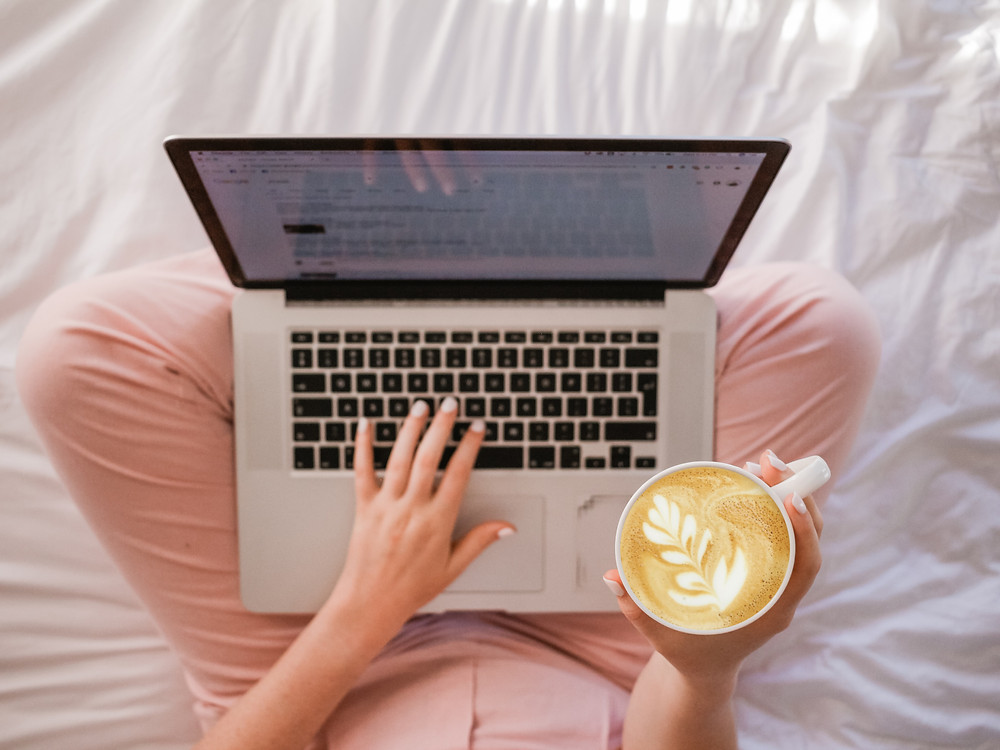 An aerial view of a person's lap as they sit on white sheets on a bed. They're wearing pink sweatpants and have their laptop open on their lap. Their left hand rests on the laptop keyboard while a cappuccino is in their right hand.