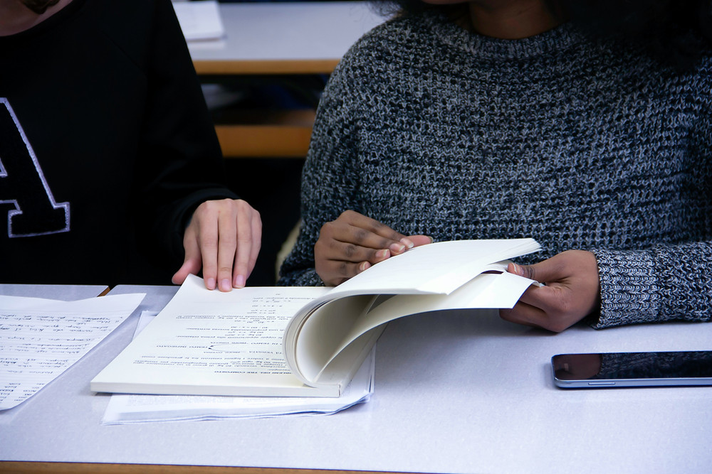A white person in a sweater and a Black person in a sweater sit at a table with open textbooks, notebooks, and papers and are flipping through the pages. A cell phone is also laid out on the table.