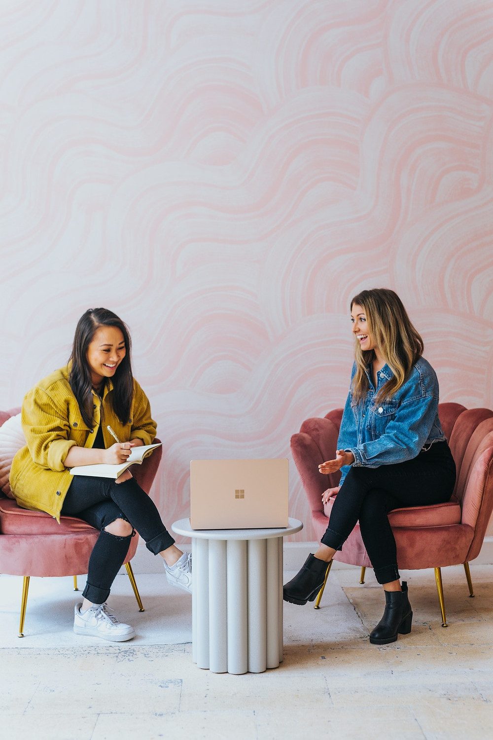 Two people sit in pink chairs with a pedestal holding a laptop between them. They're smiling and laughing.