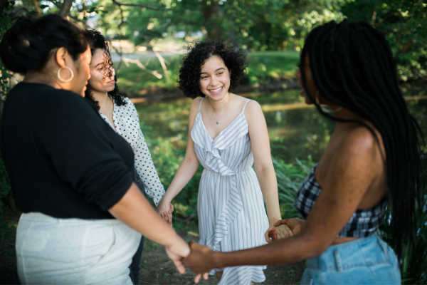 A group of 4 people stand in a circle in a green park, holding hands and smiling at each other.