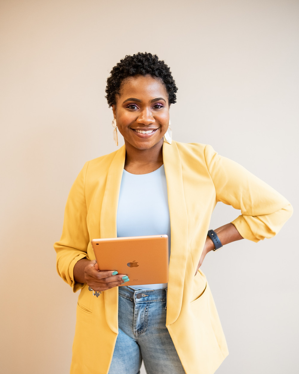 A person in a bright yellow blazer, white t-shirt, and jeans stands in the frame looking at the camera and smiling. They're holding an ipad in one hand and have their other hand on their waist.