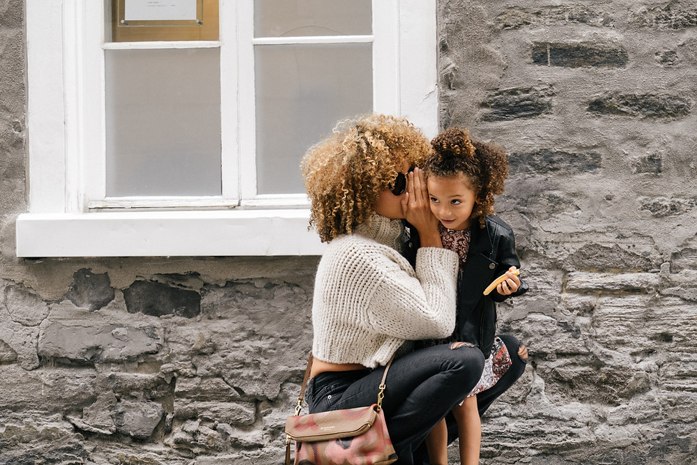 In front of a brick wall with a white window, a woman kneels down to whisper into her daughter's ear.