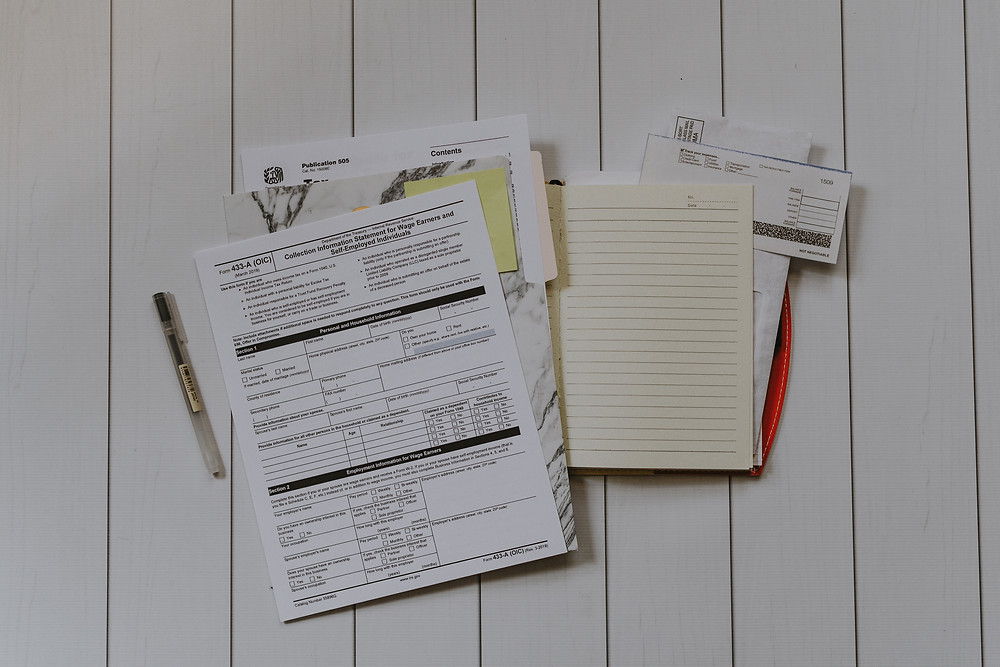 Tax documents, notebook paper, and other documents are laid out on a desk, with a pen.
