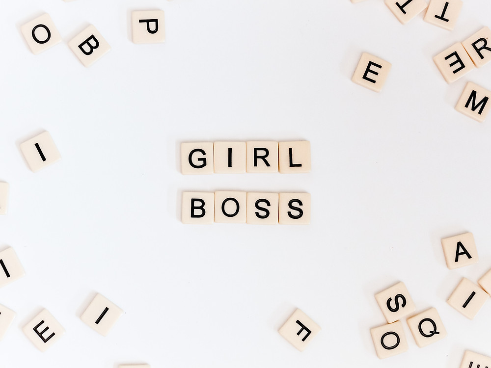 Scrabble tiles on a white background with tiles in the center spelling Girl Boss
