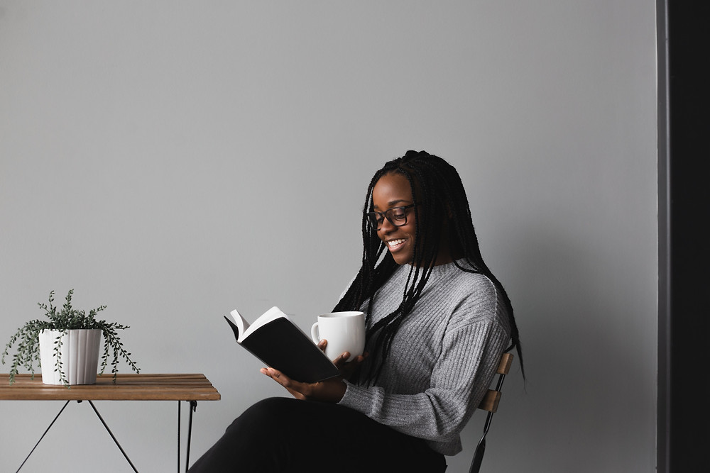 A person with long black braids and a gray sweater holds a white mug and reads while smiling from a book. There's a wooden table with a plant next to them.