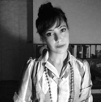 black and white photograph of the author Anjuli Raza Kolb with dark hair in a bun wearing a collared dress