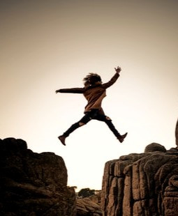Image of a woman leaping across rocks