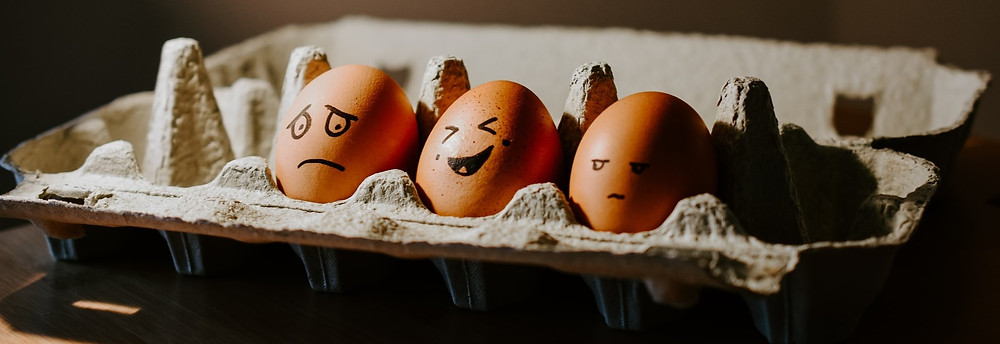 Eggs with happy and sad faces drawn on them