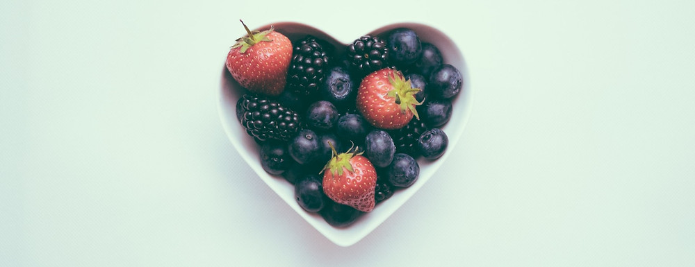 A heart shaped bowl filled with strawberries, blackberries and blueberries