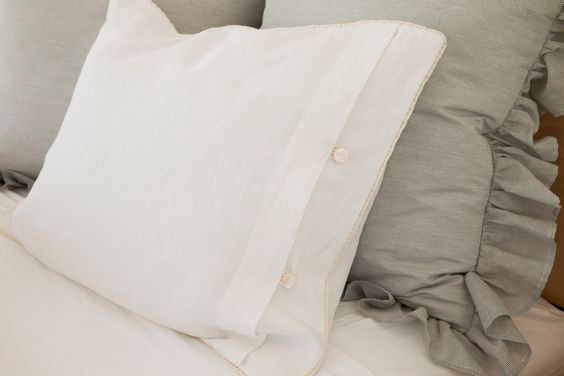 Faux pearl button closure and corded white linen fabric. Ruffled pillow made from organic cotton.