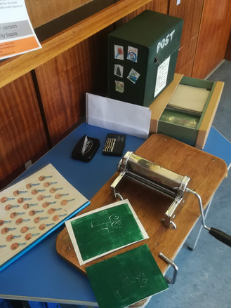 A converted pasta maker mini printing press and project post office set up in the Outpatient's waiting room