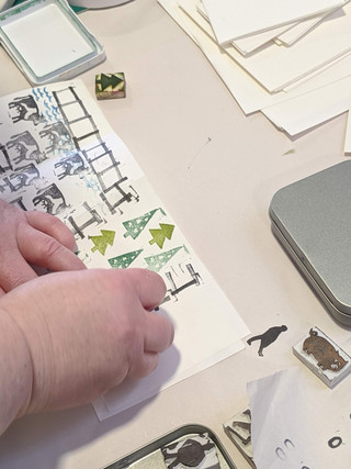 A member of staff makes a handmade book for her family using 'The Sheep Farmer' tinned stories printing kit', in the PUH foyer © Saolta Arts