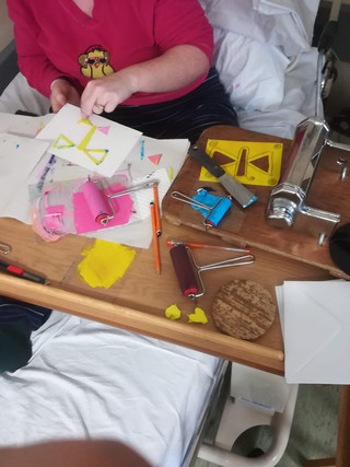 Inpatient using the modified pasta-maker printing-press on her hospital bed table, PUH