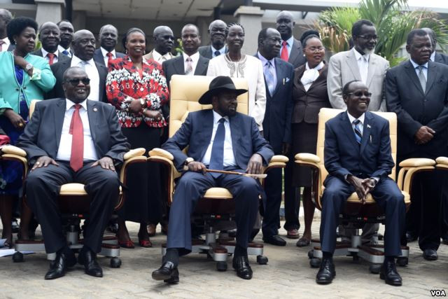 FILE - South Sudan's President Salva Kiir, center, laughs with First Vice President Riek Machar, left, and Vice President James Wani Igga, right, while cabinet members stand behind them, after the first meeting of a new transitional government of national unity, in Juba, April 29, 2016. (J. Patinkin/VOA)